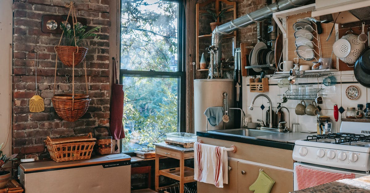 A kitchen with a stove top oven sitting next to a fireplace
