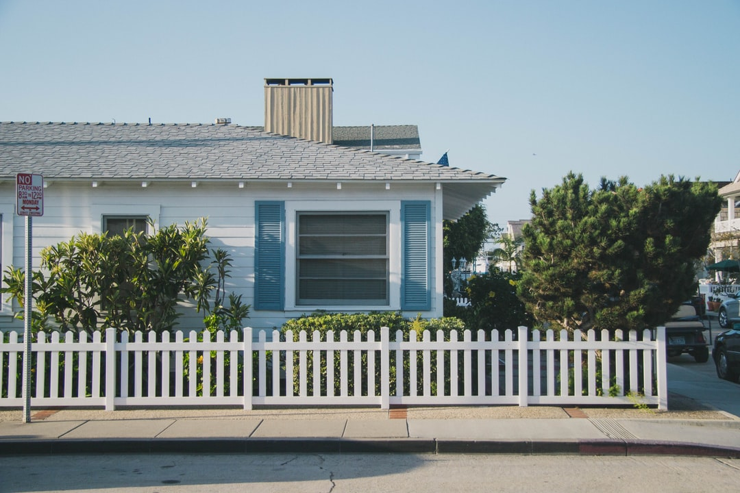 A house with a fence in front of a building